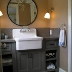 A farm sink with water faucet in white a bathroom vanity in gray black framed round vanity mirror a pair of vanity lighting