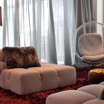 clear bubble hang chair idea with white seating pad and white back pad a modern tufted daybed with brown fluffy pillow large red fluffy area rug a clear acrylic side table