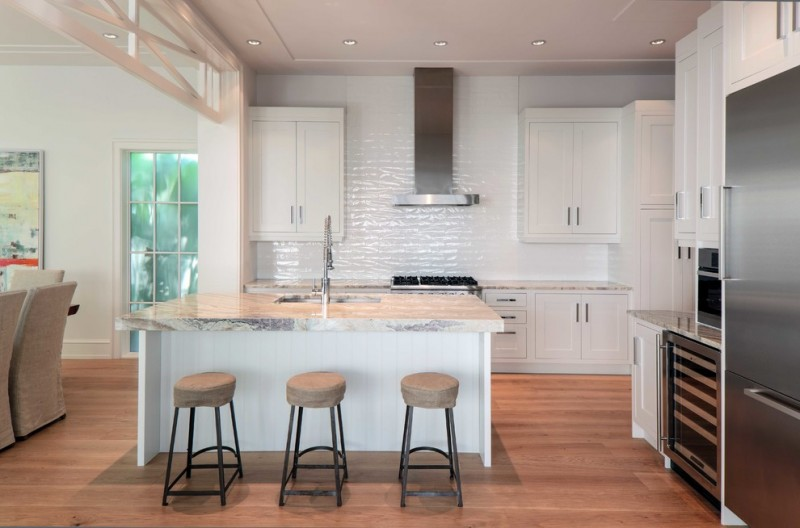 Bay themed kitchen in white glossy white bricks backsplash white cabinetry white granite countertops stainless steel appliances white island with white wooden top small stools wood color floors