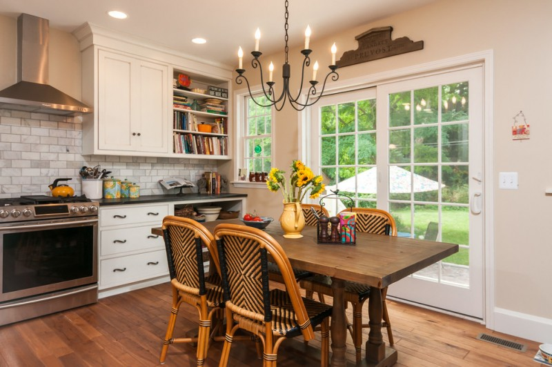 Farmhouse kitchen and dining room old yet stylish chandelier wooden dining table rattan dining chairs dark wood floors stainless steel appliances white cabinets open shelves white subway tiles backsplash