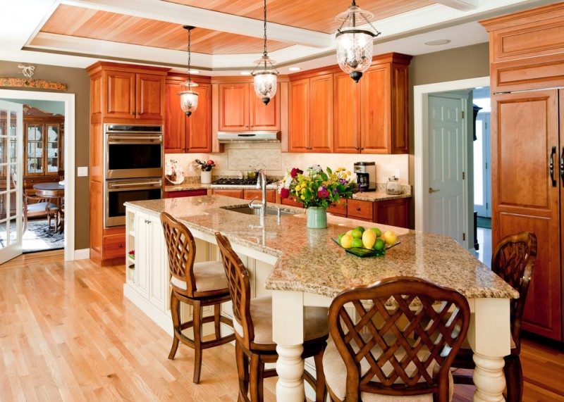L shape kitchen with granite countertop granite island stainless steel appliances wooden cabinets wooden floors without finishing two classic pendant lamps
