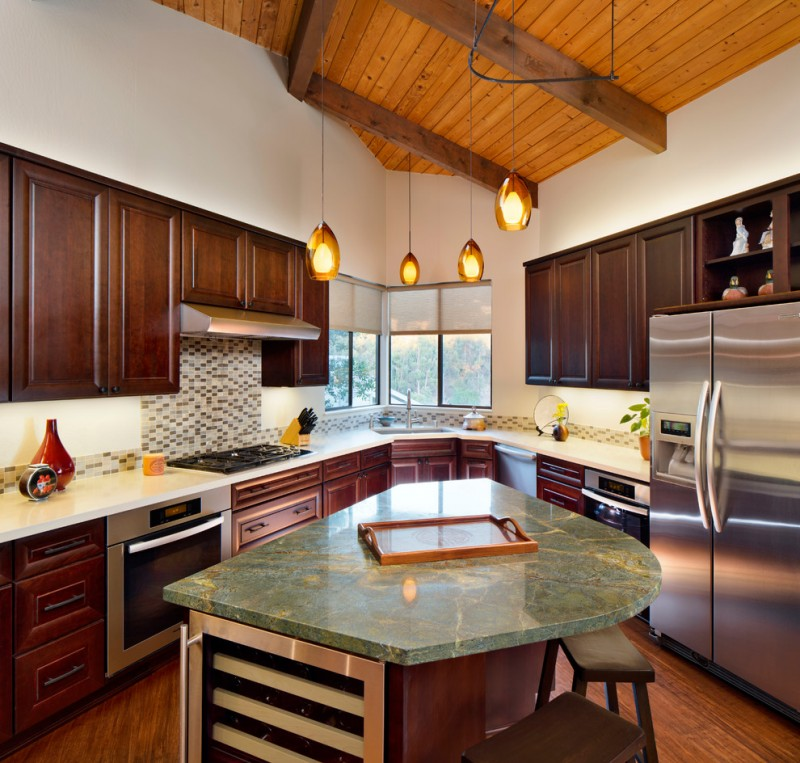L shaped kitchen with curved island in green granite top wooden stools glossy white countertop monochromatic tiles backsplash dark toned wooden cabinets clasic and warm toned pendant lamps