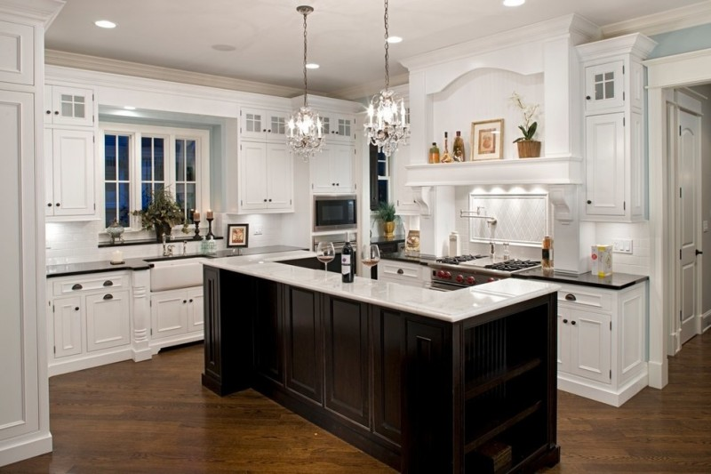 L shaped kitchen with mid sized white top island black countertop two mini chandeliers white backsplash dark toned wood floors
