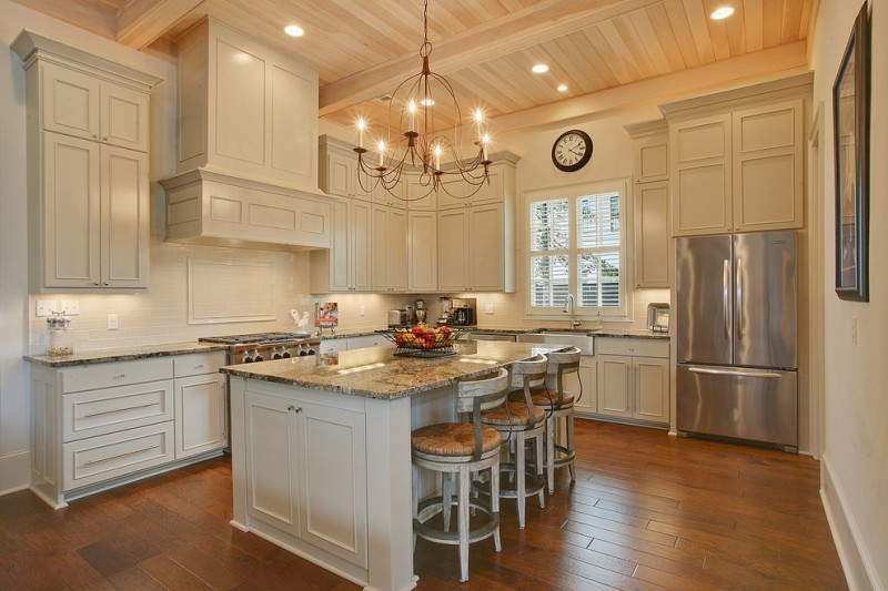 L shaped open kitchen idea with white cabinets luxurious marble island stools stainless steel appliances simple classic chandelier medium toned wooden floors white cabinets