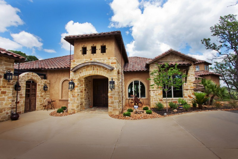 Mediterranean Tuscan home plan with Texas style light nature stone walls textured beige stucco walls red terracotta roofs idea black wrought iron wall lamps in classic style curved top entrance gate