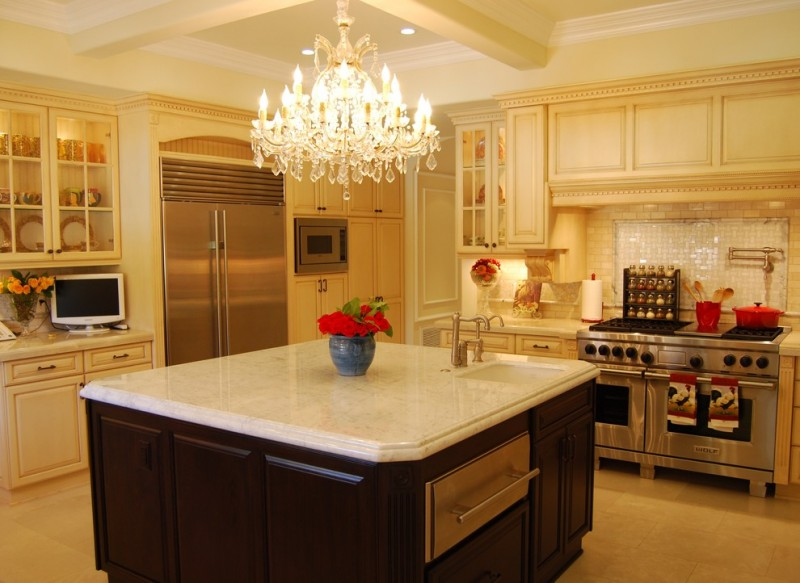 Mediterranean style kitchen with L shaped kitchen counter and island stainless steel appliances beige cabinetry glass front cabinet system luxurious classic chandelier white tiles backsplash