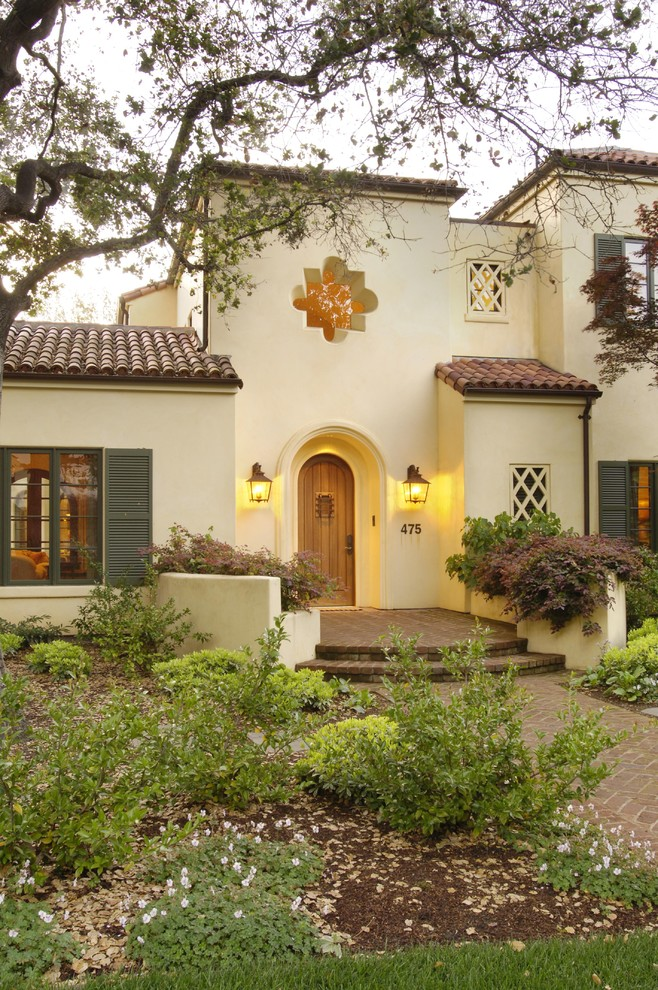 Semi modern Tuscan home design with light beige concrete walls multi level roof systems elegant arched entrance door red terracotta tiling roofs a pair of wall lamps in classic style