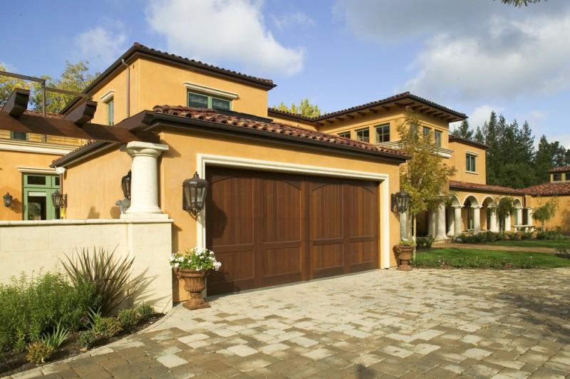 Tuscan Custom house design with dark reclaimed wood garage door dark yellow stucco walls
