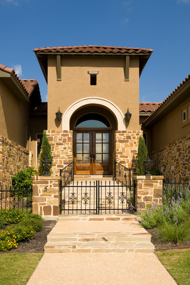 Tuscan home style with half beige stucco and stone walls classic railing system private front yard dark toned wooden entrance door with blurred glass panel