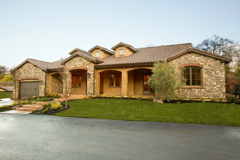 Tuscan house model with stone and stucco walls darker grey garage door simple private garden