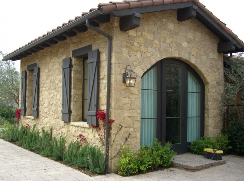 Tuscan house with limestone material black painted wooden windows and door dark brown terracotta tiles roof system mini garden surrounding at house