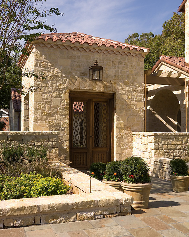 Tuscan style home design with wonderful entrance natural stone wall system handcraft wooden entrance door with metal net panel custom roof idea