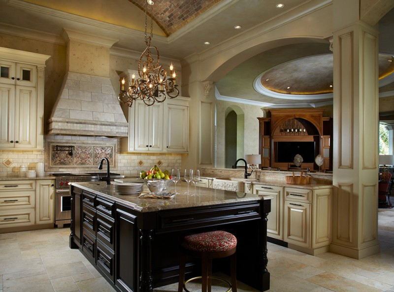 Tuscan style kitchen design L shaped kitchen counter beige cabinets colorful backsplash classic chandelier over island oversized island with dark marble top farmhouse sink colorful and round top stool