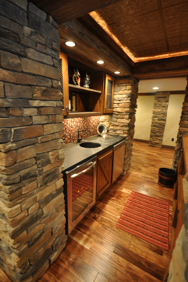 Western themed basement bar glossy grey countertop round and deep sink mosaic subway tiles backsplash glass front under cabinets net front upper cabinets medium toned wooden floors rustic bricks wall