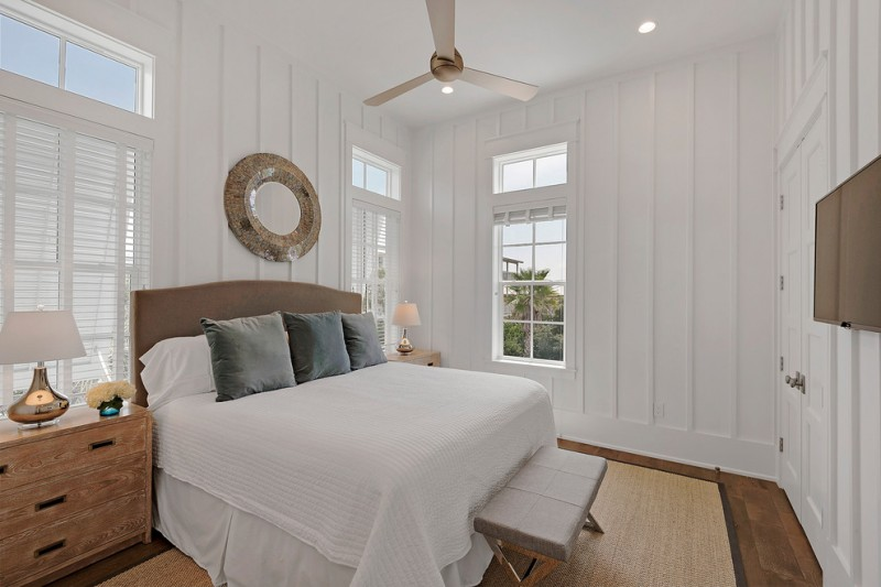 Western themed bedroom design for beach house white bed linen beige headboard wooden bedisde table without finishing wood fiber mat ceiling fan medium tone wood floors