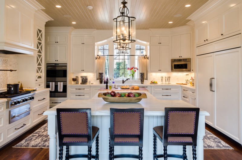 asymmetrical French Style Kitchen white countertop L shape island stainless steel appliances white cabinets lights under cabinets classic pendant lamps black stools with detail accessories