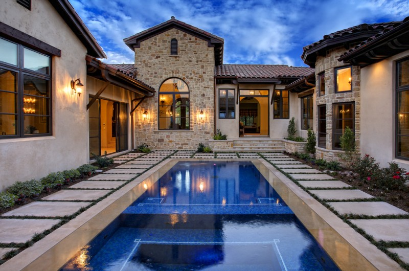 authentic Tuscan house with stone wall systems beige stucco walls dark framed glass windows and doors courtyard retreat outdoor pool