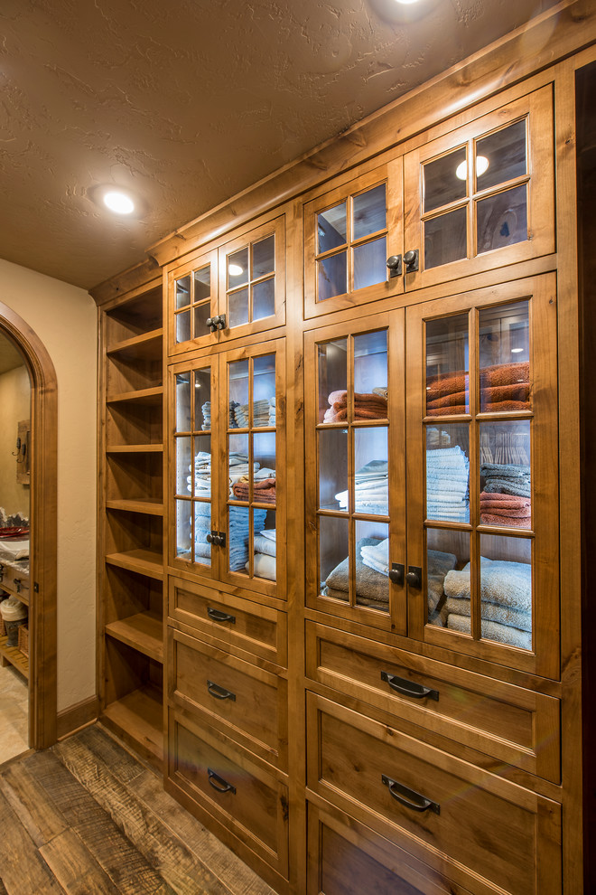 bottom to top walk in closet idea with recessed glass panel cabinets drawer arrangement and open shelves