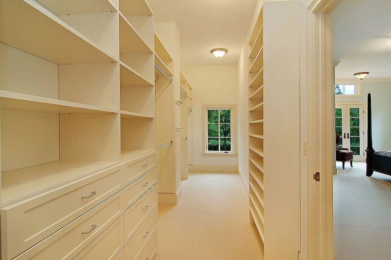 charm and warm tone walk in closet with medium sized glass window and bulb ceiling lamp