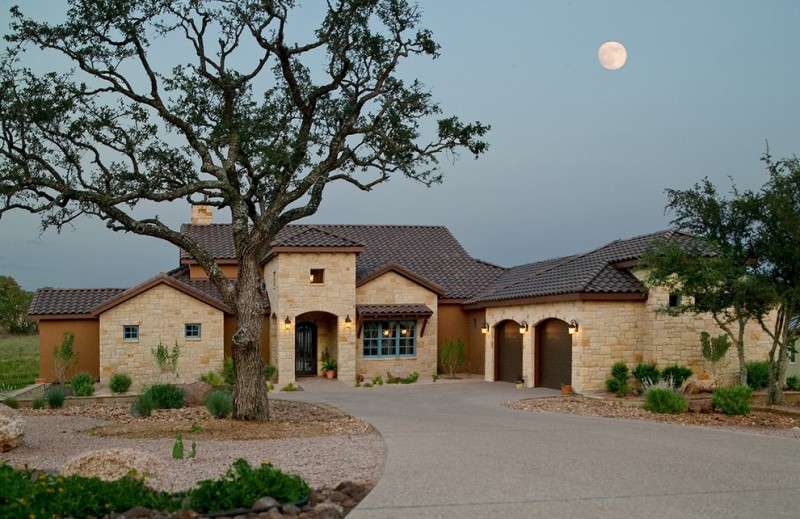 classy and original Tuscan style house with beige stone walls narrow and curved windows and doors blue framed windows dark terracotta roofs