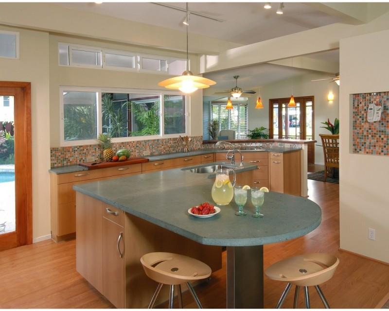 contemporary kitchen with multicolor mosaic backsplash L shape countertop in grey custom island with grey solid concrete surface and wooden base wood flooring series of glass windows