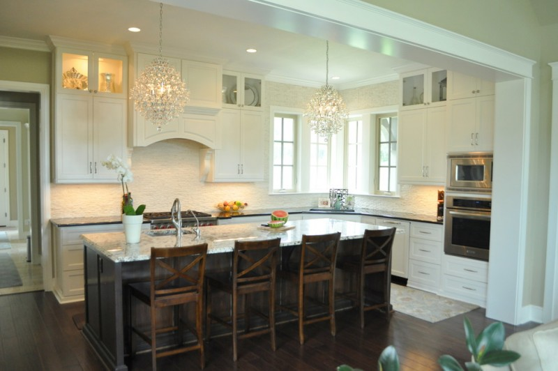 country french L shape kitchen with beautiful chandeliers black countertop extra size island rustic wooden stools white cabinets stainless steel appliances dark tone floors textured white backsplash