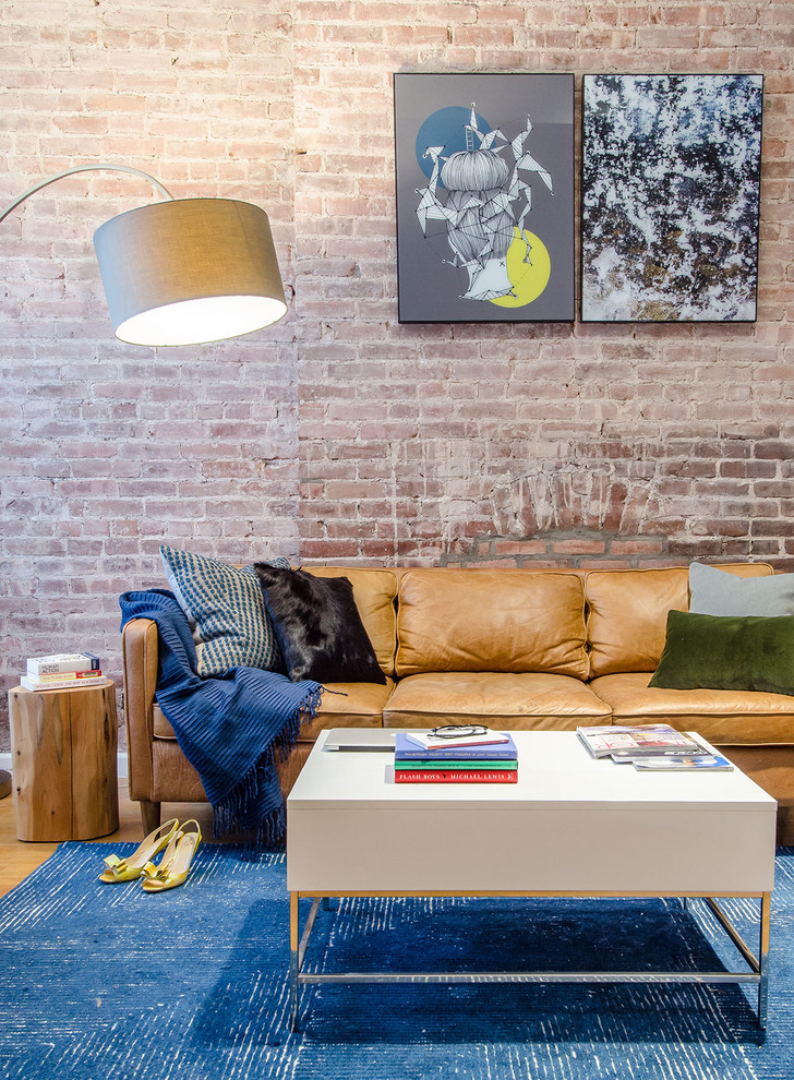 cozy family room with light tone leather sofa with colorful accent pillows minimalist white center table bright blue rug log side table red brick walls some wall arts