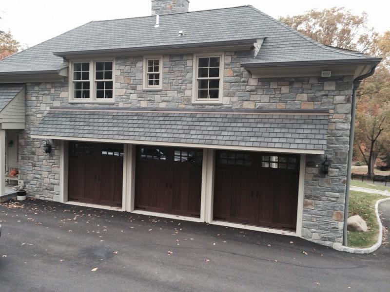 dark woodgrain finish garage door idea with grey natural stone garage wall and grey shade