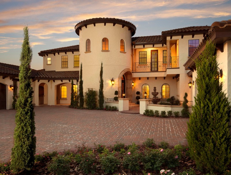 grand Tuscan style villa with earthy beige stucco walls dark brown terracotta roofs curved top doors and windows stone floor for yard exterior yard