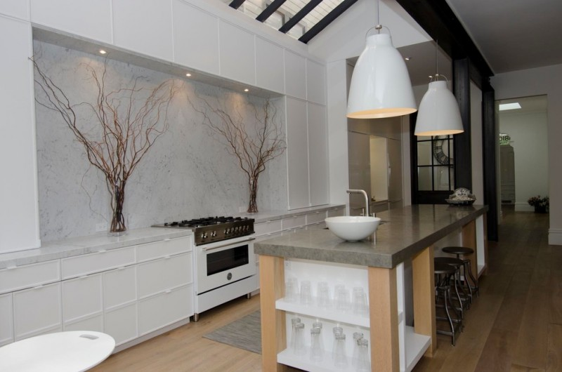 industrial kitchen with mini bar large white pendant lamps free standing white sink and single faucet black stools flat white cabinets white backsplash with decorative dried trees grey concrete island