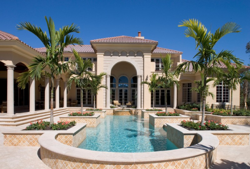 luxurious and large Tuscan style home with pool big arched doors dark red terracotta roof tiles carved limestone flooring arched roof elements light beige walls
