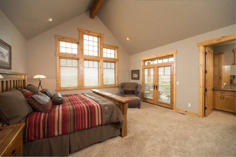 master suit bedroom idea for a ranch home vaulted ceiling medium tone window frames medium tone bed beige and smooth rug a corner chair glass window and door with metal shutters