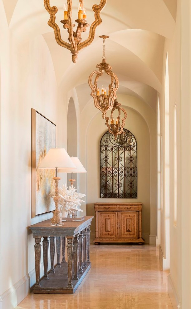 mediterranean hallway with luxurious lighting fixtures classy console tables soft walls glossy beige floors curved top interior window with craftsman metal panels