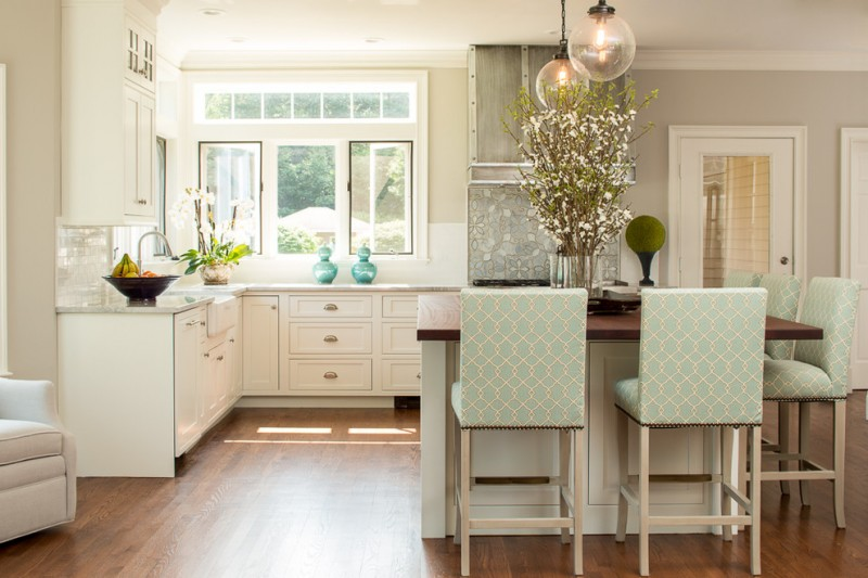 modern kitchen & dining room with classic touch turquoise barstools L shape countertop in white white cabinets corner windows wooden top island medium tone wood floors white subway tiles backsplash