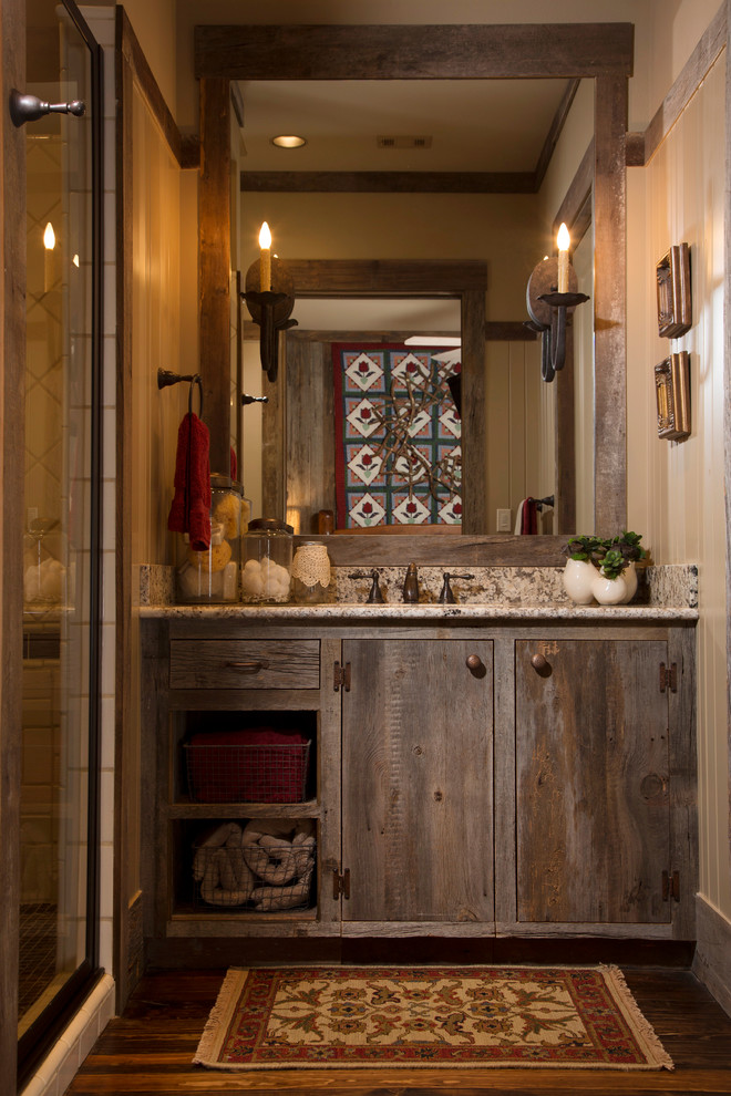narrow rustic bathroom vanity with marble countertop and cabinetry shabby wood frame vanity mirror a couple of candle like vanity lamps