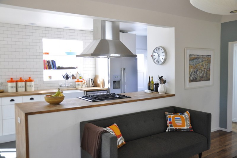 open kitchen design in small size with hardwood countertop white tiles wall system dark gray sofa with orange accent pillows