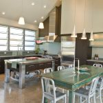 Open Kitchen Idea With Dining Furniture Stainless Steel Appliances Stainless Steel Counter And Island White Vaulted Ceiling Modern Glass Pendant Lamps Light Blue Kitchen Walls