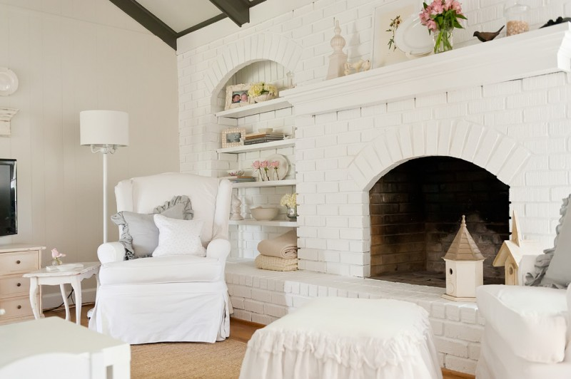 shabby but chic white bricks fireplace idea in a full white living room