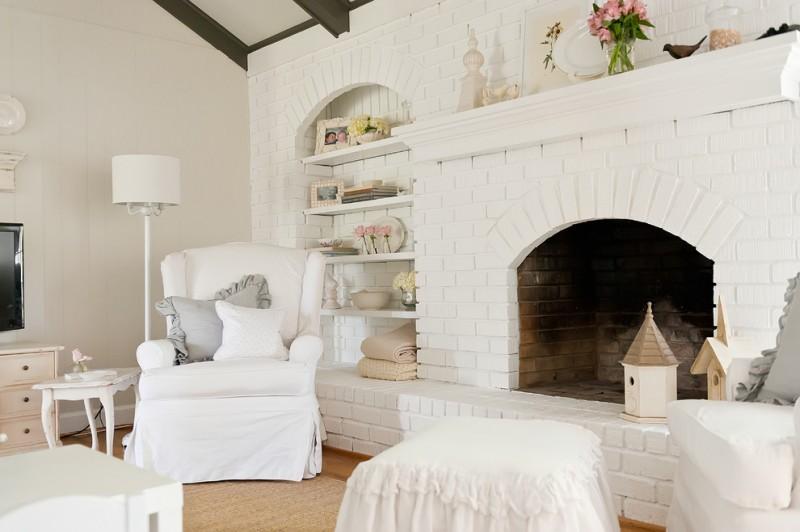 shabby but chic white bricks fireplace idea in a full white living room