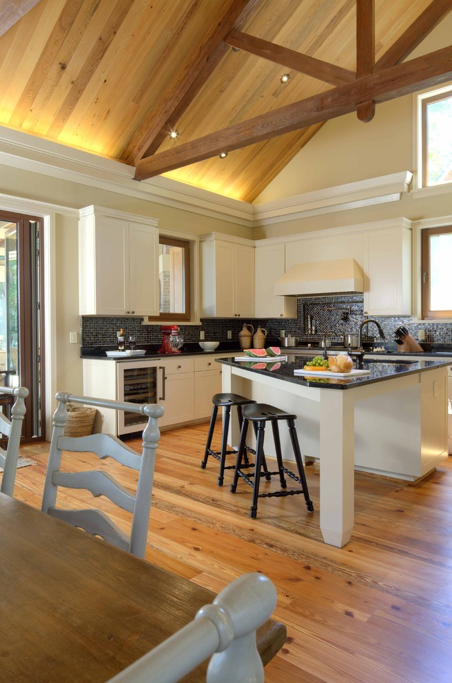 small L shape kitchen island similar to roof cedar floors triangular shape roof and beams black subway tiles backsplash white flat panel cabinetry stainless steel appliances
