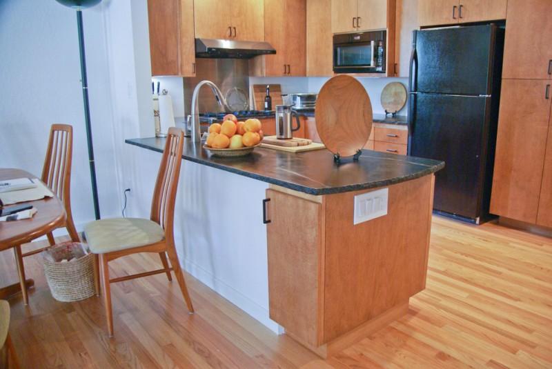 small eat in L shape kitchen idea with medium tone floors black appliances black soapstone countertop black soapstone island flat panel cabinets in medium tone drop in sink
