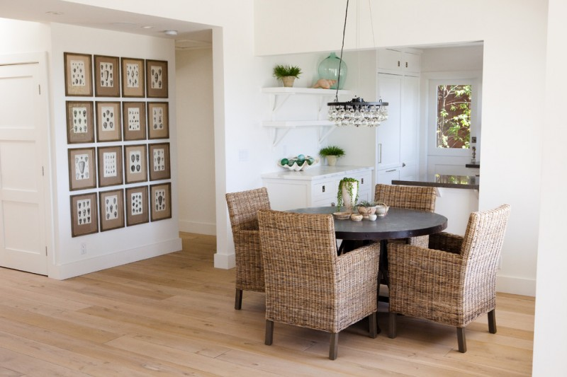 small kitchen and dining room rattan dining chairs black round dining table small white countertop white open shelves light tone wood floors creative walll accent