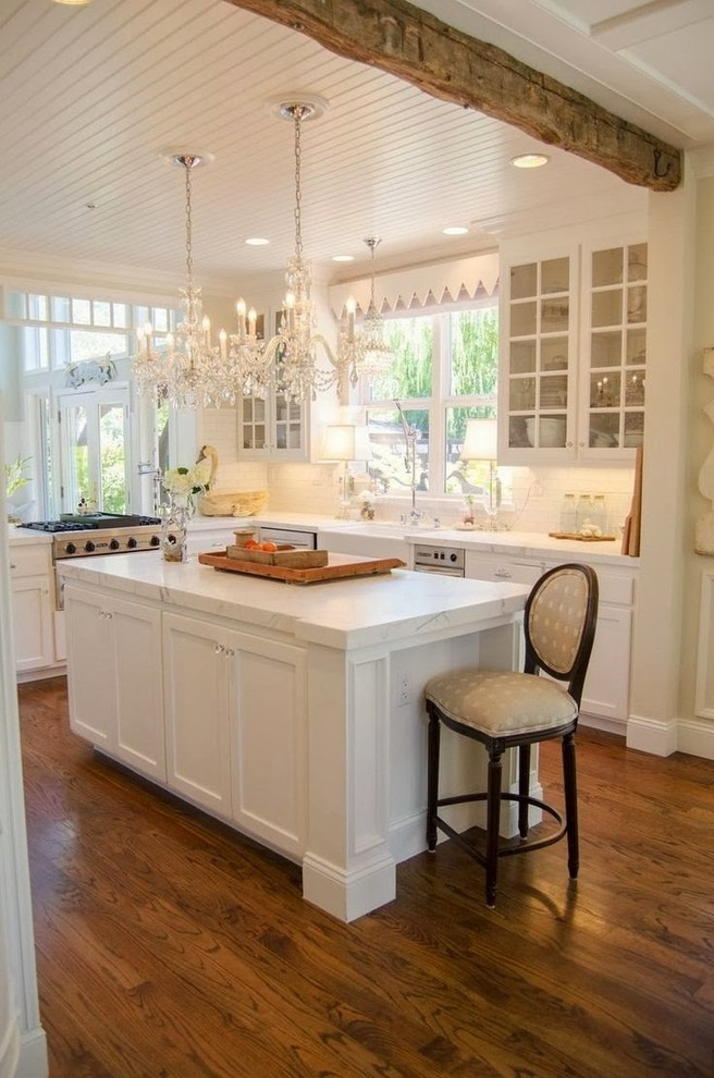 traditional L shaped kitchen with white island white kitchen counter white cabinet glass door cabinetry dark toned wooden floors stainless steel appliances