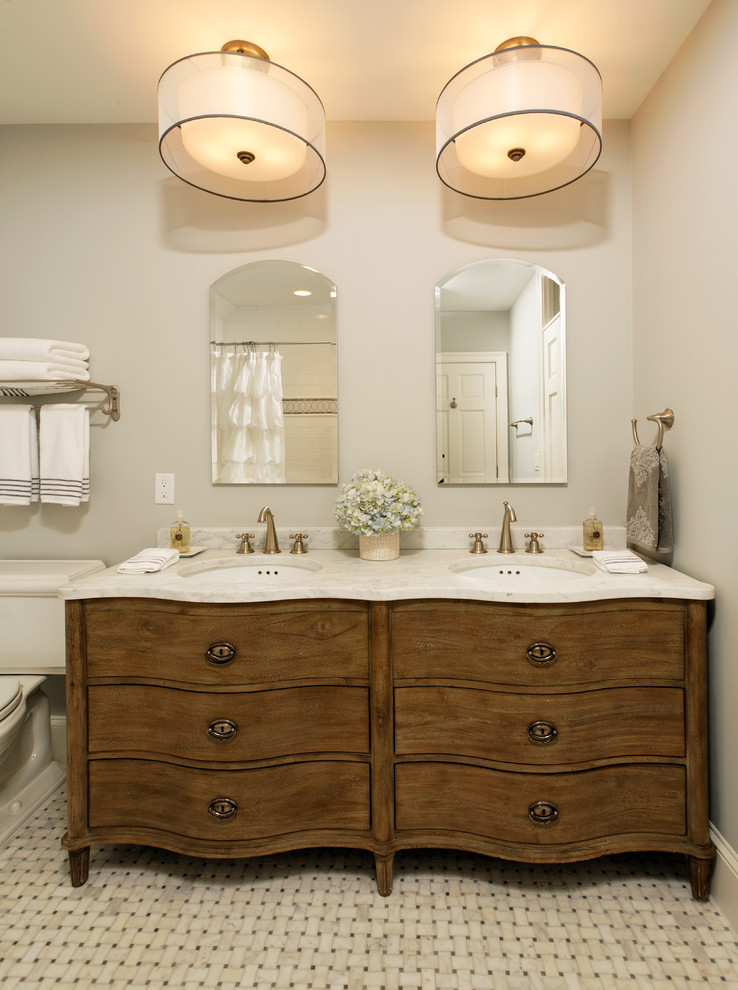traditional bathroom vanity with double white basins and double gold toned faucets huge modern pendant lamps frameless vanity mirrors dual doors wooden cabinetry