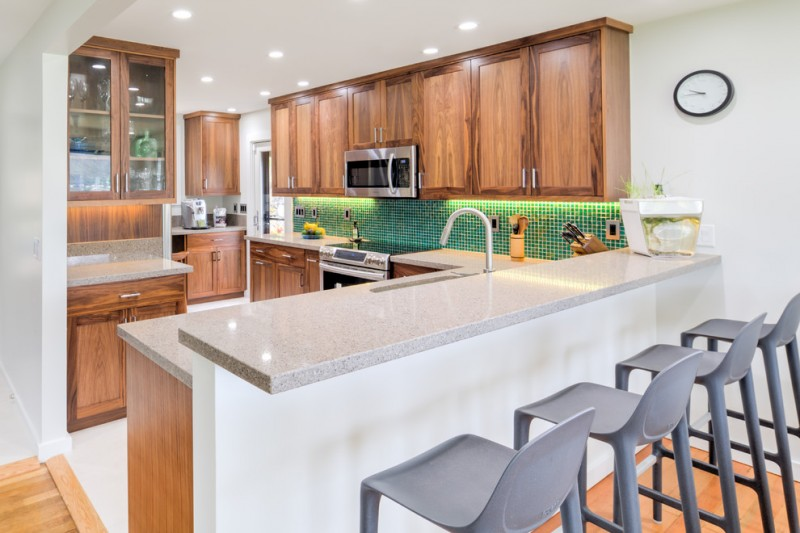 transitional kitchen idea with eat in area green tiles backsplash white granite countertop stainless steel appliances dual layers kitchen island light grey stools wooden cabinets