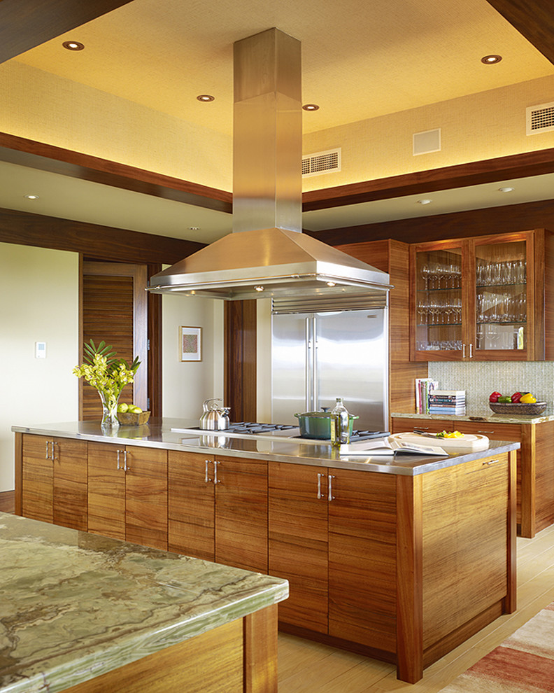 tropical themed kitchen with Western tones grey top island with wooden base wooden upper cabinets with glass front stainless steel appliances light tone wood floors