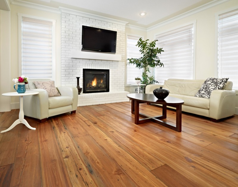 white bricks fireplace with black frame and glass cover wall mounted TV on top a white armchair with an accent pillow a white and round side table hardwood floor idea