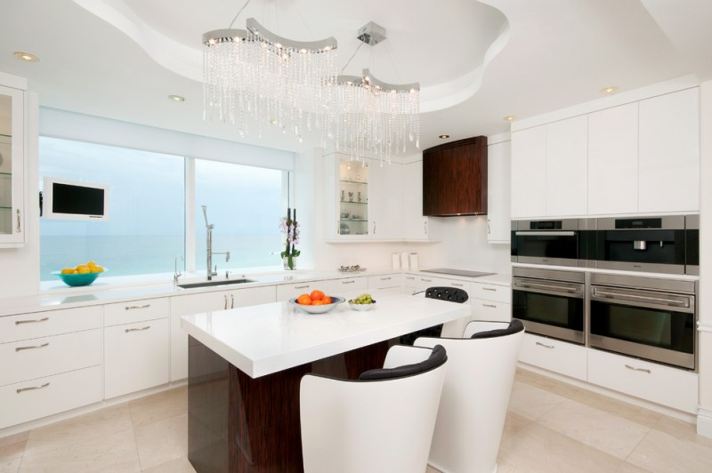 white dominant glamour kitchen with L shape counter and dark surfaced mdoern stools stainless steel appliances and superb & luxurious crystal chandeliers