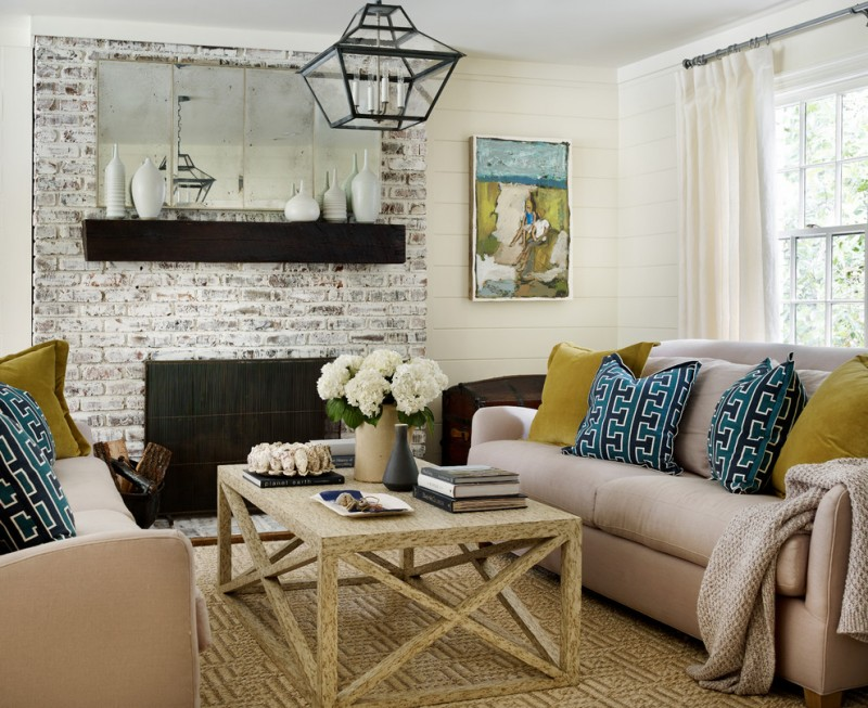white washed fireplace with dark cover X base center table warm cream sofas with accent pillows cream rug unique pendant lamp