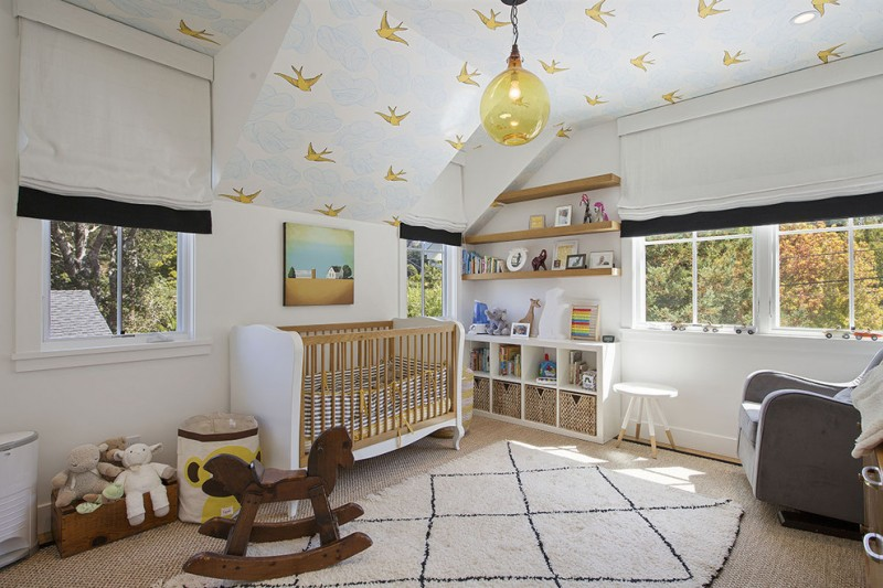 Scandinavian style nursery idea white fluffy rug with black line ornaments dark grey nursery chair wood baby crib with white sideboard kids' rocking chair in animal shape white ceillings with bird pri